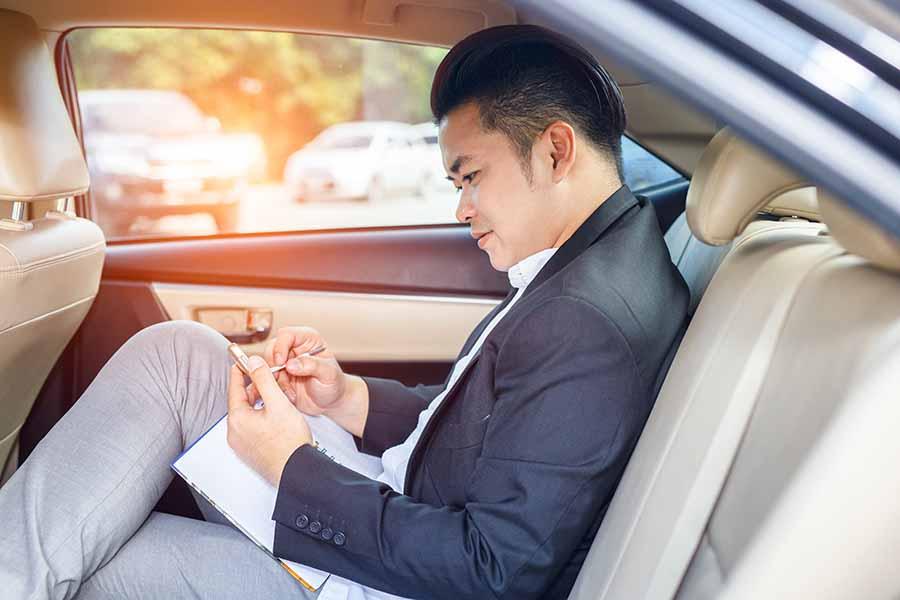 Businessman sitting in back seat enjoying corporate limousine service