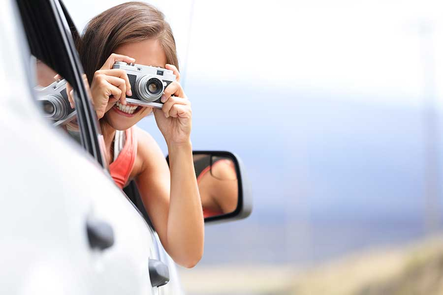 Female tourist leaning out of a limousine to take photos