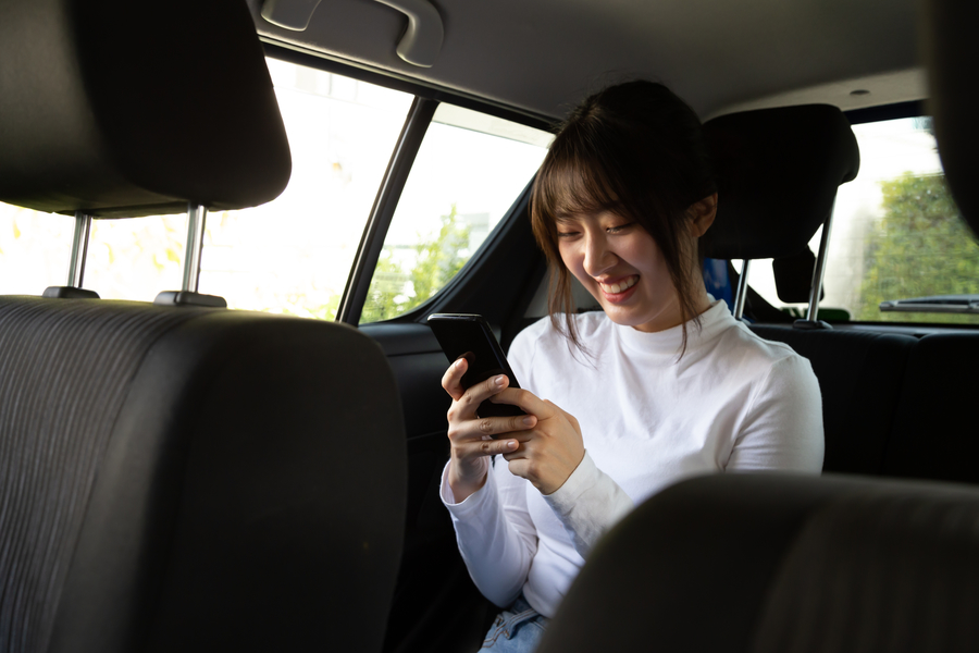 Woman sitting in back seat enjoying ride from chauffeur service singapore company