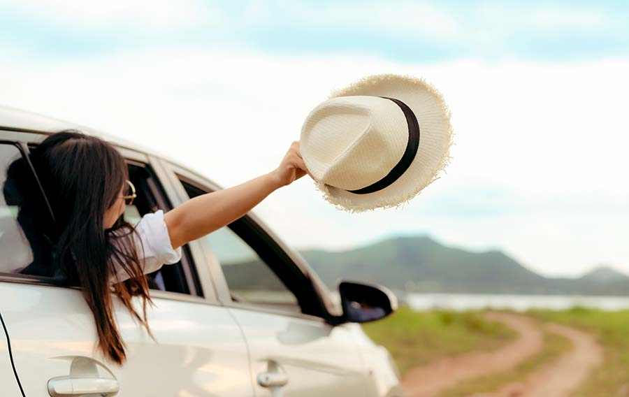 lady on vacation holding hat outside limousine window
