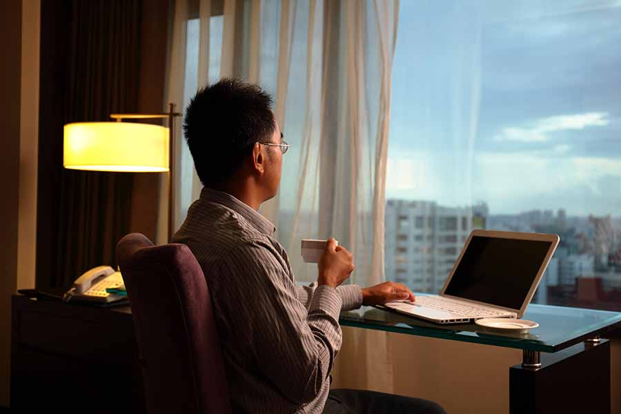 business man comfortably working on laptop in hotel room