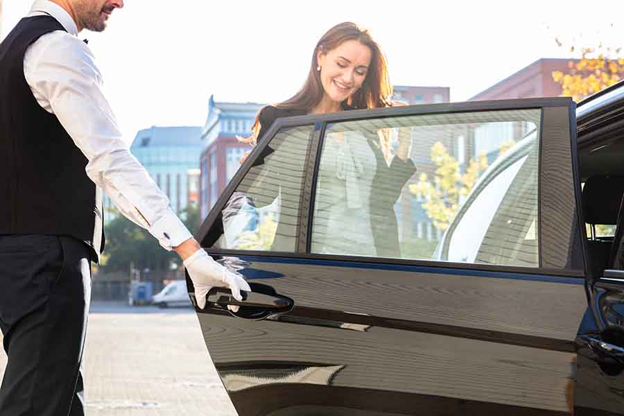 chauffer opening door for female guest to enter limousine
