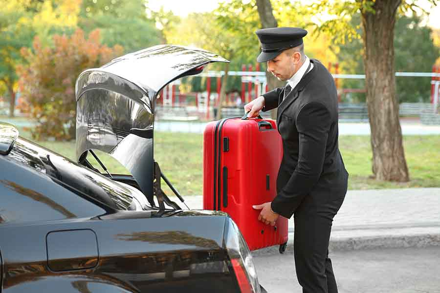 chauffeur loading guest luggage in boot of limousine