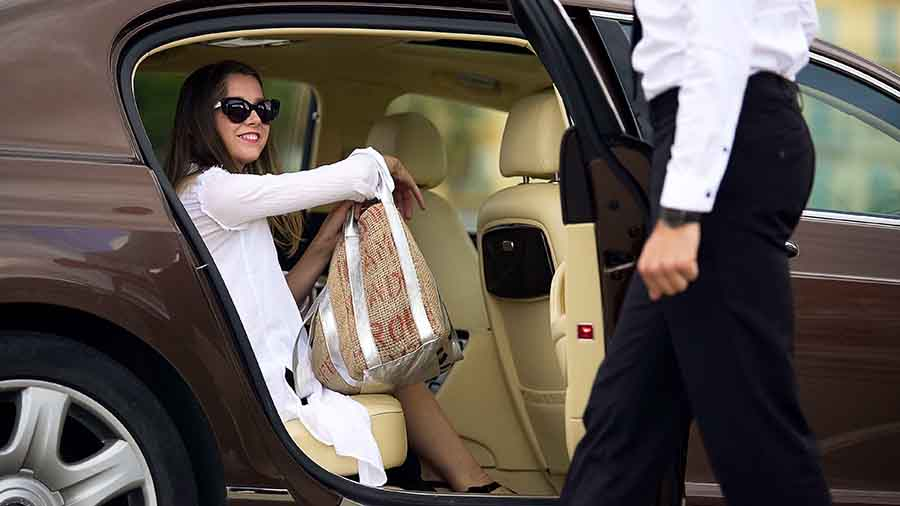 chauffeur opening door for vip guest to exist limousine
