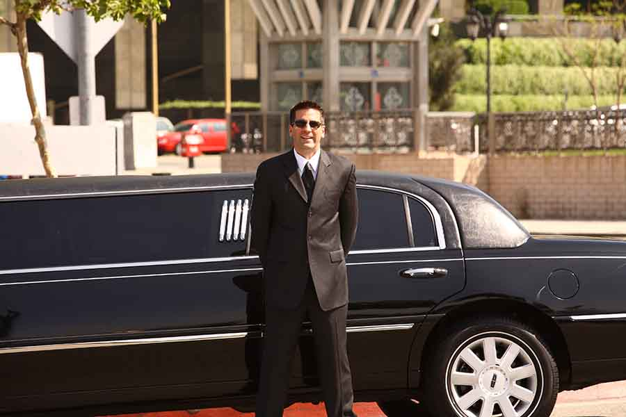 chauffeur waiting with limousine service for guests