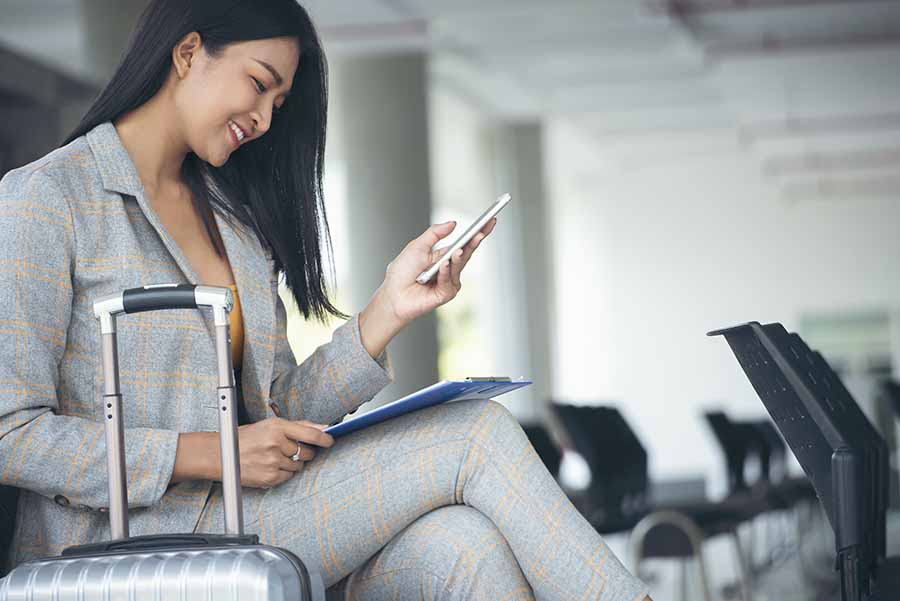 female business traveller sitting at airport with phone and luggage