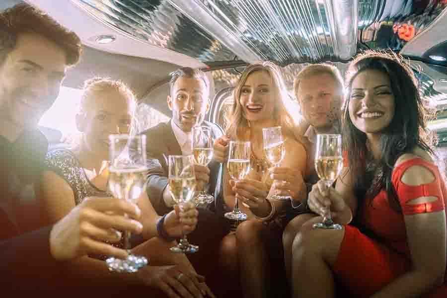 group of adults enjoying drinks in limousine